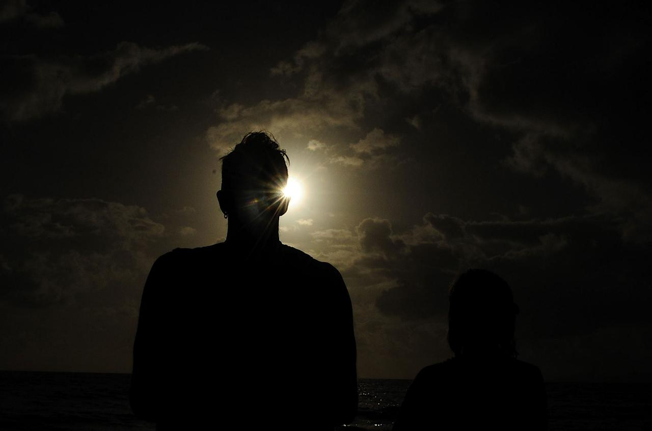 PALM COVE, AUSTRALIA - NOVEMBER 14:  A spectator views the solar eclipse  on November 14, 2012 in Palm Cove, Australia. Thousands of eclipse-watchers have gathered in part of North Queensland to enjoy the solar eclipse, the first in Australia in a decade.  (Photo by Ian Hitchcock/Getty Images)