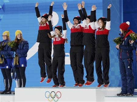 Gold medallists Canada's Jennifer Jones, Kaitlyn Lawes, Jill Officer, Dawn McEwen and Kirsten Wall (3rd L-2nd R) jump on the podium as silver medallists Sweden's Margaretha Sigfridsson and Agnes Knochenhauer (L-2nd L), and bronze medallist Britain's Eve Muirhead (R) look on during the victory ceremony for the women's curling competition at the 2014 Sochi Winter Olympics February 22, 2014. REUTERS/Jim Young