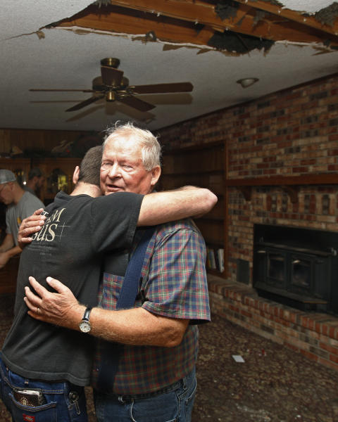 FILE - Joe Reneau, right, gets a hug from friend Cody Parsons in his family room in Sparks, Okla. on Sunday, Nov. 6, 2011 after the room was damaged when the chimney collapsed during an earthquake and fell partially through the roof, at upper right. Neither Joe nor his wife were in the room at the time, and were not injured. A team of scientists have determined that a 5.6 magnitude quake in Oklahoma in 2011 was caused when oil drilling waste was injected deep underground. The report was released Tuesday, March 26, 2013 by the journal Geology. That makes it the most powerful quake to be blamed on deep injections of wastewater, although not everyone agrees. Oklahoma's state seismologists say the quake was natural. (AP Photo/Sue Ogrocki)