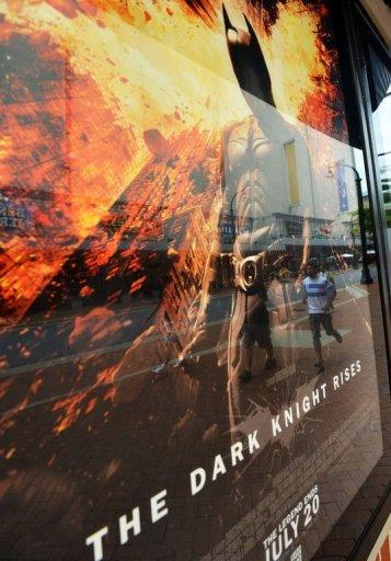 """People walk past a poster of the new Batman movie """"The Dark Knight Rises"""" outside a theater in Silver Spring, Maryland. With a fixation on random violence, Gotham City dysfunction and the death of a star, the """"Batman"""" movies have long been consumed with tragedy and terror. Now an unfathomable horror is forever linked to the series"""