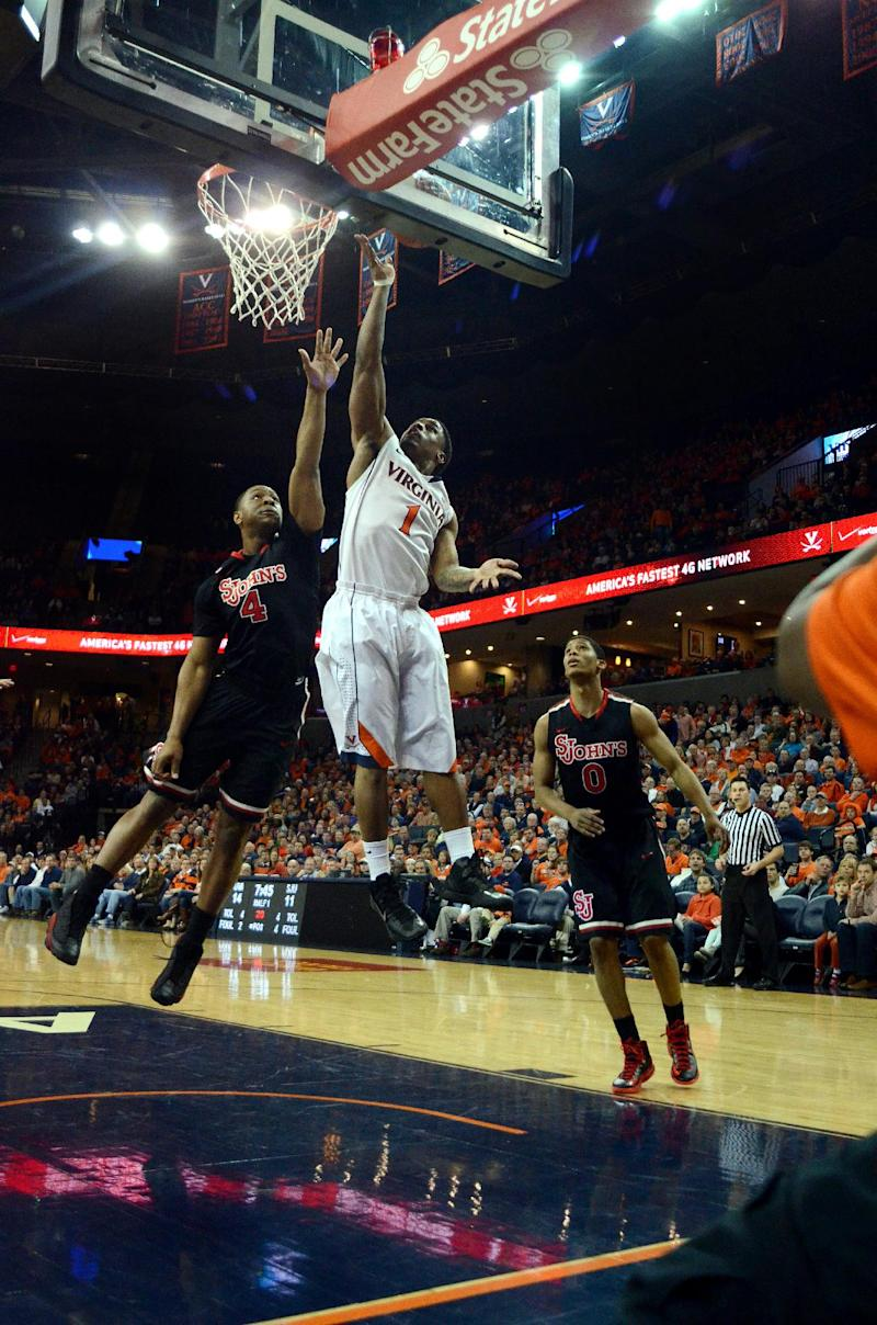 Virginia's Jontel Evans, center, scores over St. John's Christian Jones, left, and Jamal Branch during an NIT college basketball game in Charlottesville, Va., Sunday, March 24, 2013.   (AP Photo/Pat Jarrett)