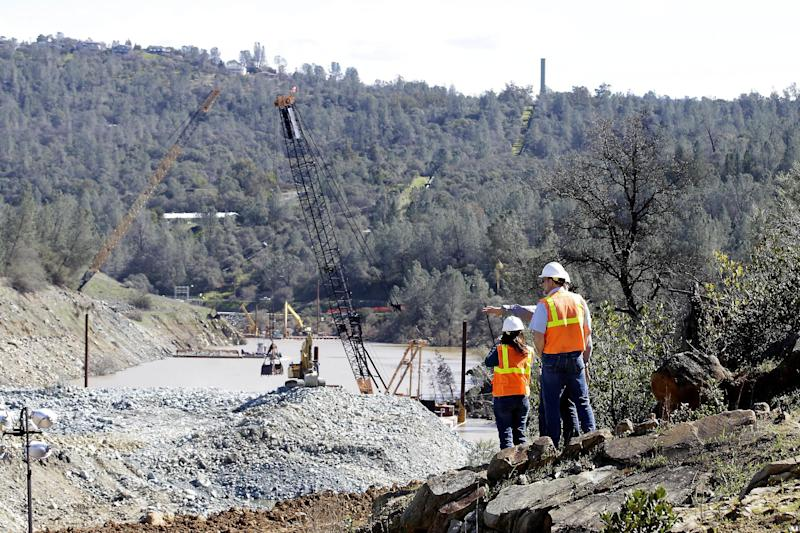 Construction crews dredge the river bed near Oroville Dam's crippled spillway Tuesday, Feb. 28, 2017, in Oroville, Calif. California water authorities stopped the flow of water down the spillway, Monday, allowing workers to begin clearing out massive debris that's blocking a hydroelectric plant from operating. (AP Photo/Rich Pedroncelli)