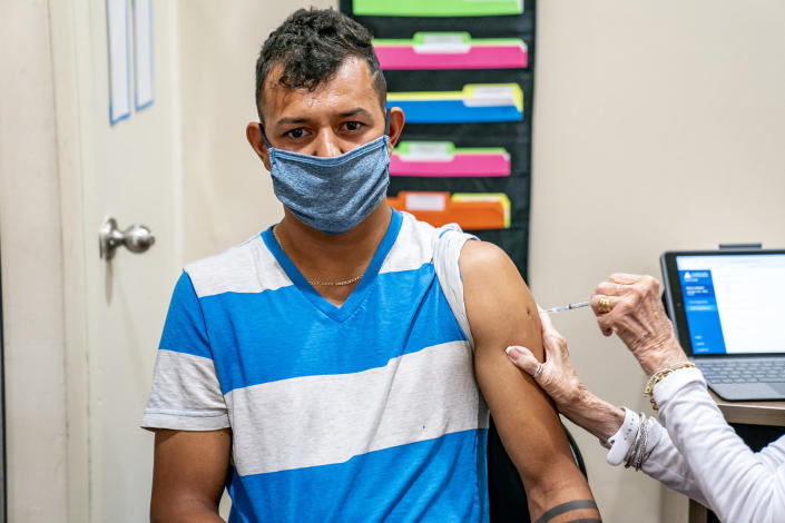 Juan Rios, of Ambridge, receives a dose of the COVID-19 vaccine at a clinic run by the Allegheny County Health Department at Casa San Jose, a non-profit serving Latino immigrants, Tuesday, Sept. 14, 2021, in the Beechview neighborhood of Pittsburgh. (Alexandra Wimley/Pittsburgh Post-Gazette via AP)