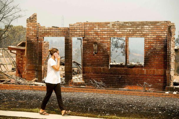 PHOTO: A woman surveys damage to her grandmother's house after the Carr Fire burned through Redding, Calif., July 27, 2018. (Noah Berger/AP)