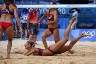<p>Latvia's Tina Graudina (C) falls in the sand in their women's preliminary beach volleyball pool D match between the USA and Latvia during the Tokyo 2020 Olympic Games at Shiokaze Park in Tokyo on July 26, 2021. (Photo by ANGELA WEISS / AFP)</p>