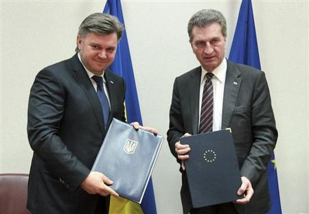 Ukrainian Energy and Fuel Minister Stavytsky stands with European Energy Commissioner Oettinger after signing an agreement on energy cooperation at an EU-Ukraine summit in Brussels
