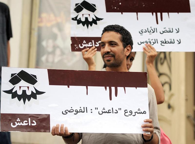A Tunisian protester holds a 'Daesh' placard during a demonstration against the Islamic State in Tunis, on September 25, 2014 (AFP Photo/Fethi Belaid)
