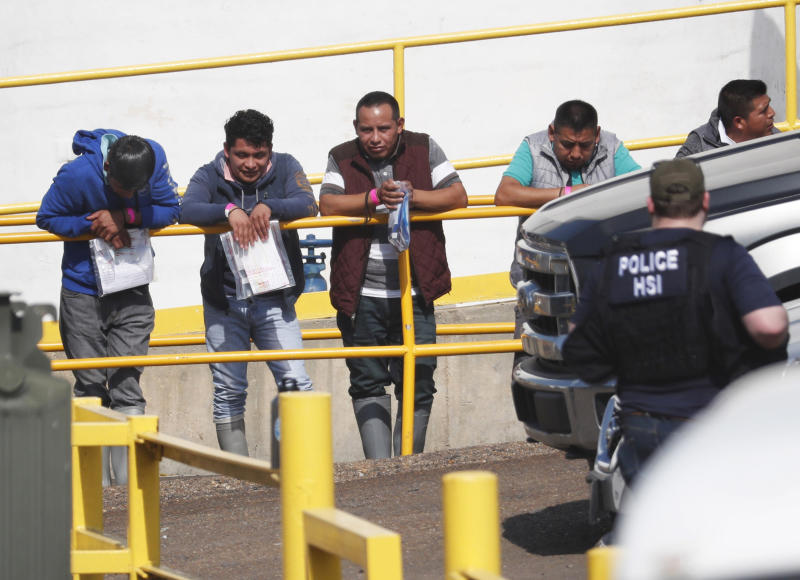 Handcuffed workers await transportation to a processing center following a raid by U.S. immigration officials at Koch Foods Inc., plant in Morton, Miss. | Rogelio V. Solis—AP