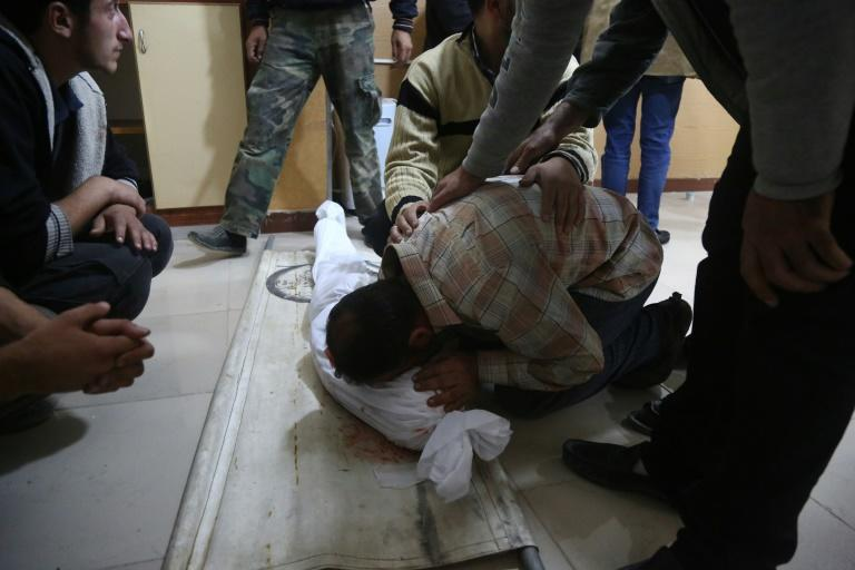 A Syrian man mourns over the body of a child at a makeshift hospital following the reported government shelling of a school in the rebel-held besieged town of Jisreen, east of the capital Damascus, on October 31, 2017