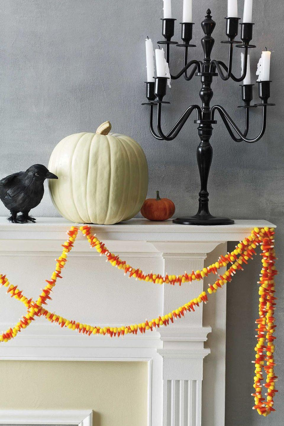 <p>String candy corn pieces together to form a sweet-as-can-be garland that can be draped over windows, door frames, and mantels — if you can get through the DIY without eating the entire bag, that is. </p>