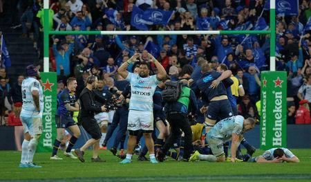 Rugby Union - European Champions Cup Final - Leinster Rugby v Racing 92 - San Mames, Bilbao, Spain - May 12, 2018 Leinster Rugby players celebrate after the game as they celebrate winning the European Champions Cup while Racing 92's Census Johnston reacts REUTERS/Vincent West
