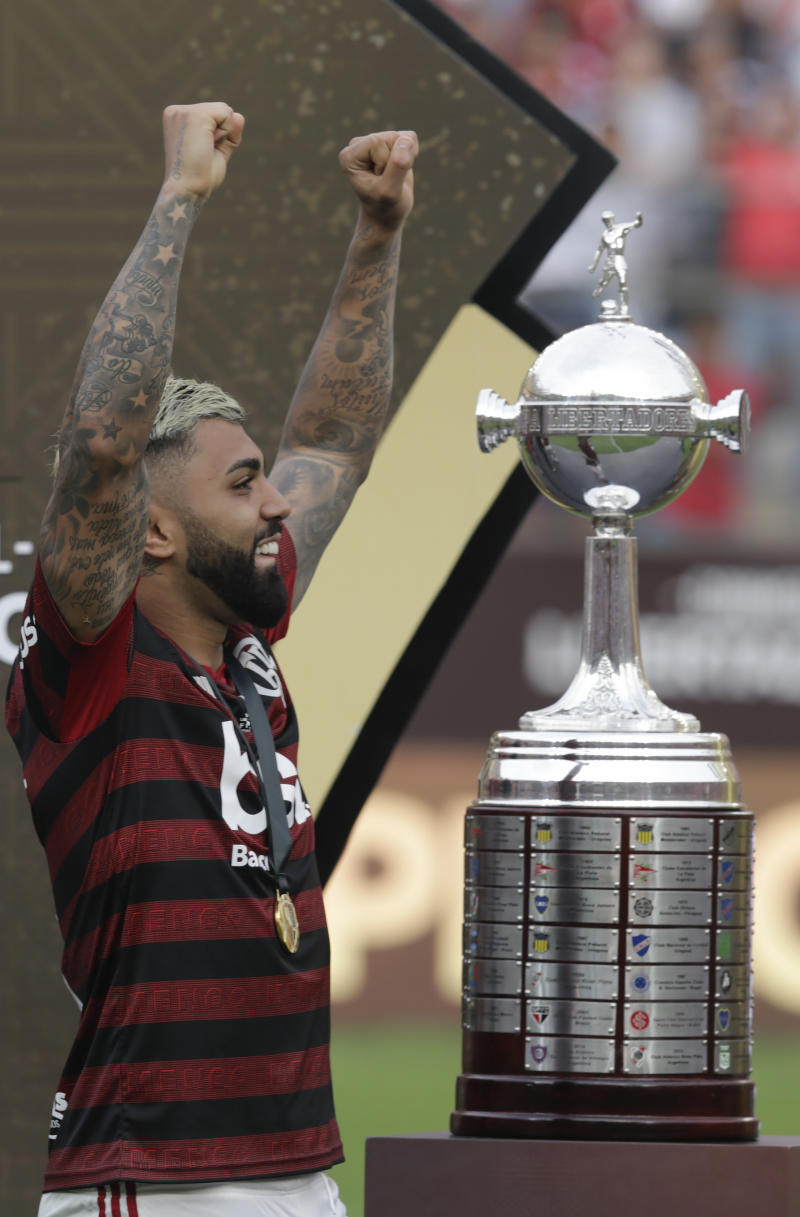 Gabriel of Brazil's Flamengo celebrates next to the trophy after his team defeated Argentina's River Plate 2-1 to win the the Copa Libertadores final soccer match at the Monumental stadium in Lima, Peru, Saturday, Nov. 23, 2019. (AP Photo/Martin Mejia)