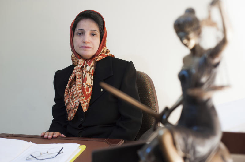 FILE - In this Nov. 1, 2008 file photo, Iranian human rights lawyer Nasrin Sotoudeh, poses for a photograph in her office in Tehran, Iran. Sotoudeh is jailed in Iran's most feared prison Evin prison. In some cells in Iran, Syria and other countries in the Middle East, prisoners are crammed in by the dozens, with little access to hygiene or medical care. So if one infection gets in, the novel coronavirus could run rampant. The virus causes mild or moderate symptoms for most people, but for some, especially older adults and people with existing health problems, it can cause more severe illness or death. (AP Photo/Arash Ashourinia, File)