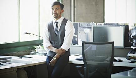Smiling businessman at workstation in office