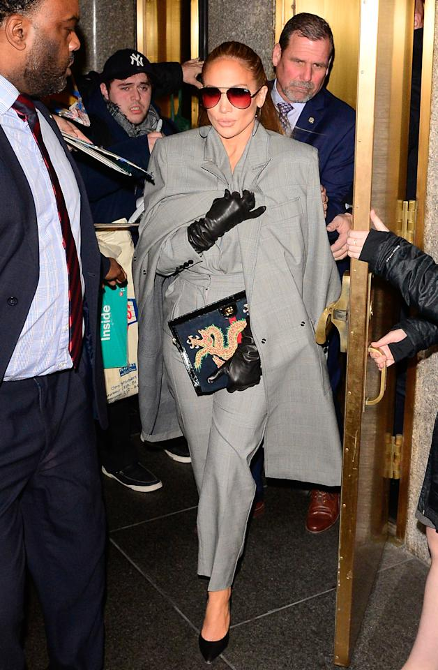 "<p>The ""Jenny from the Block"" singer changed into a tailored grey suit by Max Mara as she left NBC studios. Lopez added some interest to the business-chic look with black gloves and a Gucci clutch. </p>"
