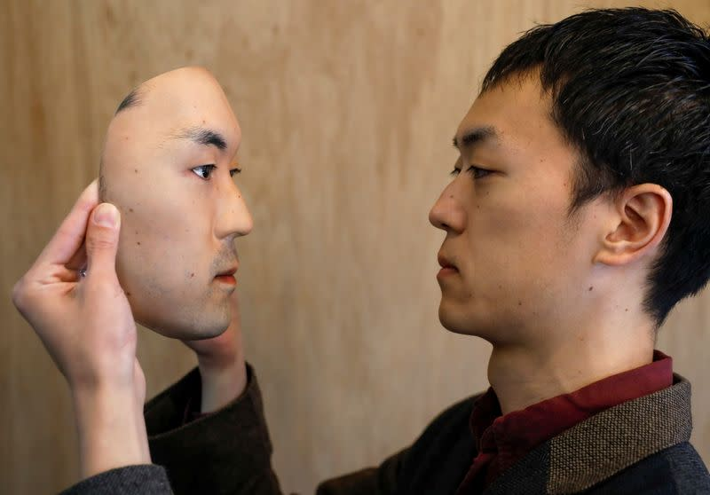 Shuhei Okawara, 30, owner of mask shop Kamenya Omote, holds a super-realistic face mask based on his real face, made by using 3D printing technology, in Tokyo