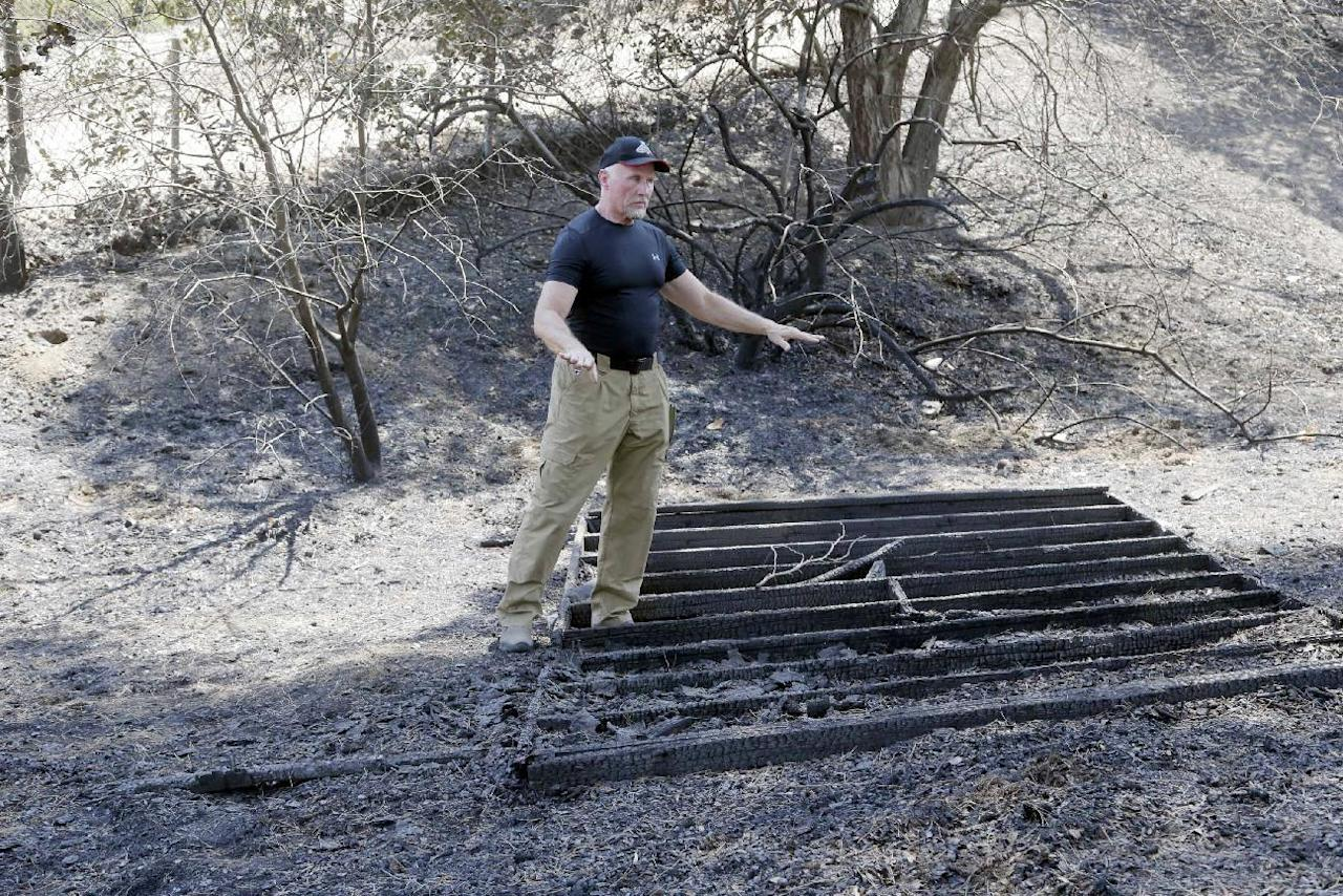 Lane Leavitt, who trains stunt actors and specializes in setting people on fire for movies and television, shows Tuesday, July 26, 2016, where fire came close to his home that escaped damage when the Sand fire swept through Santa Clarita, Calif. over the weekend. The fire destroyed 18 homes and authorities said that by Tuesday it had burned more than 37,000 acres, about 58 square miles. (AP Photo/Nick Ut)