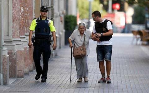 Policemen accompany an elderly woman near a cordoned off area - Credit:  PAU BARRENA