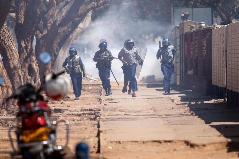 Zimbabwean anti-riot police pursue supporters of the opposition party Movement for Democratic Change Tsvangirai faction during a rally in Harare on August 24, 2016 (AFP Photo/Wilfred Kajese)