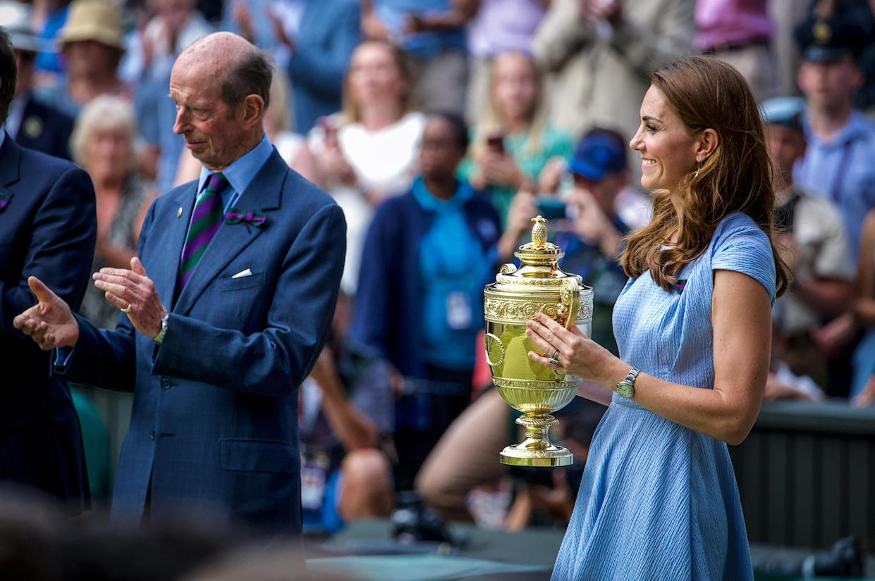 Prince Edward, Duke of Kent, stands next to Catherine, Duchess of Cambridge, as she holds the trophy before presenting it to Novak Djokovic of Serbia after he defeated Roger Federer of Switzerland in the Men's Singles Final on Centre Court during the Wimbledon Lawn Tennis Championships at the All England Lawn Tennis and Croquet Club at Wimbledon on July 14, 2019 in London, England.