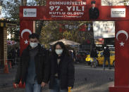People wearing masks to help protect against the spread of coronavirus, walk along a popular street in Ankara, Turkey, Friday, Nov. 27, 2020. Turkey's COVID-19 fatalities continue to rise, hitting another record Sunday, Nov 29, 2020, with 185 new deaths. The Turkish government resumed reporting all positive cases this week after only reporting symptomatic patients for four months. Night-time curfews over the weekend are in effect for a second week across the country but media reports show packed public spaces during the day. (AP Photo/Burhan Ozbilici)