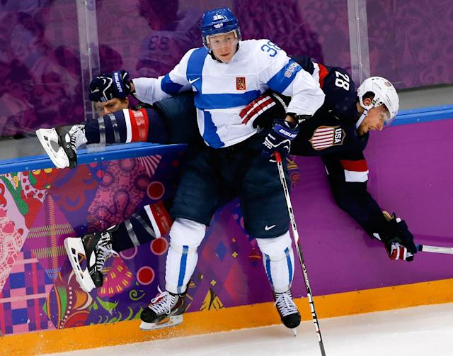 Juuso Hietanen of Finland (38) pins Blake Wheeler of the United States (28) up against the boards during the third period of the men's bronze medal ice hockey game at the 2014 Winter Olympics, Saturday, Feb. 22, 2014, in Sochi, Russia. (AP Photo/Julio Cortez)