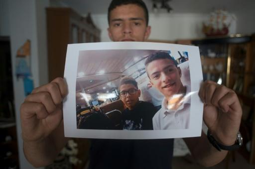 Anass Tahiri, 22, holds a picture of him and his brother, Iliass, who died while being restrained in a juvenile detention centre in Spain