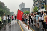 Anti-coup protesters hold Chinese flag in Yangon