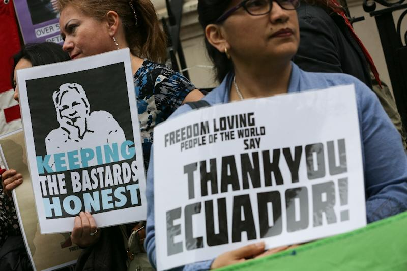 Supporters hold up signs as they gather outside the Ecuadorian embassy in central London on June 19, 2016, where WikiLeaks founder Julian Assange has hold up for four years (AFP Photo/Daniel Leal-Olivas)