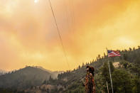Jessica Bell watches as the Dixie Fire burns along Highway 70 in Plumas National Forest, Calif., on Friday, July 16, 2021. (AP Photo/Noah Berger)