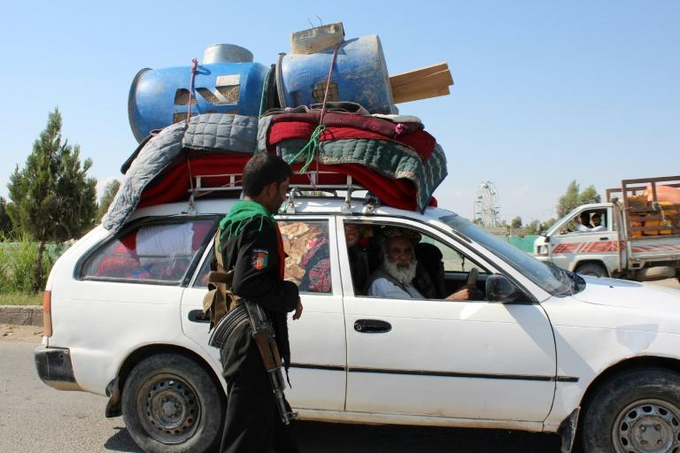 A policeman stands guard at a road checkpoint as an internally displaced family flees from the ongoing fighting between Afghan security forces and Taliban fighters, on the outskirts of Lashkar Gah on May 5, 2021