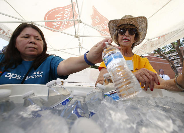 <p>Salvation Army volunteers Evangeline Ford, left, and Jackie Rifkin, right, restock a cooler with bottles of water at a hydration station for people as they try to keep hydrated and stay cool as temperatures climb to near-record highs, June 19, 2017, in Phoenix. (Ross D. Franklin/AP) </p>