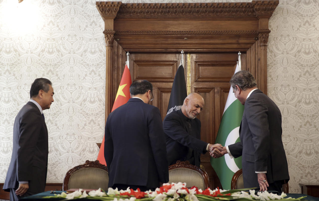 Afghanistan's President Ashraf Ghani shakes hands with Pakistan's Foreign Minister Shah Mehmood Qureshi, first right, after signing the agreement during a meeting at the presidential palace in Kabul, Afghanistan, Saturday, Dec. 15, 2018. Afghanistan, Pakistan, and China are meeting in the Afghan capital to discuss trade, development and ending the region's relentless conflicts. (AP Photo/Massoud Hossaini)