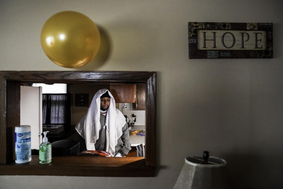 Myon Burrell walks through the kitchen of his home in Minneapolis, Thursday, Dec. 17, 2020, two days after his release from prison. On Tuesday, Minnesota's pardon board commuted the sentence of Burrell, 34, a Black man who was sent to prison for life as a teen in a high-profile murder case that raised questions about the integrity of the criminal justice system. (AP Photo/John Minchillo)