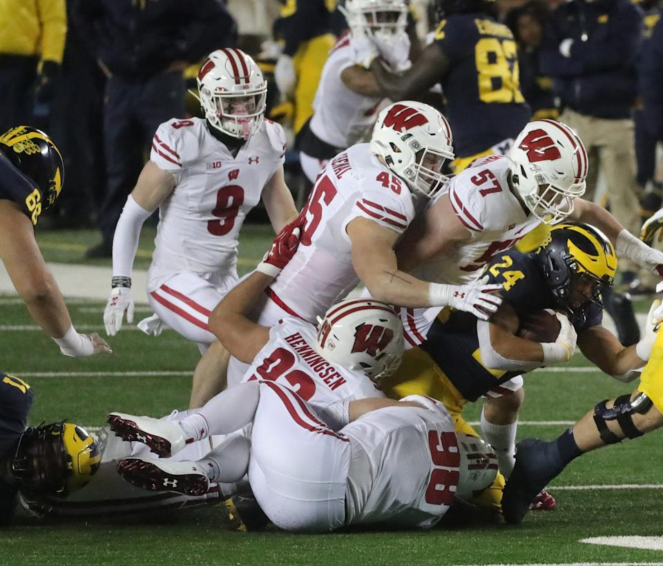 Michigan Wolverines running back Zach Charbonnet is tackled by Wisconsin Badgers defenders during the first half at Michigan Stadium in Ann Arbor, Nov. 14, 2020.