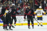Carolina Hurricanes center Jordan Staal, front right, celebrates his goal against the Nashville Predators with defenseman Brett Pesce (22) during the third period in Game 1 of an NHL hockey Stanley Cup first-round playoff series in Raleigh, N.C., Monday, May 17, 2021. (AP Photo/Gerry Broome)