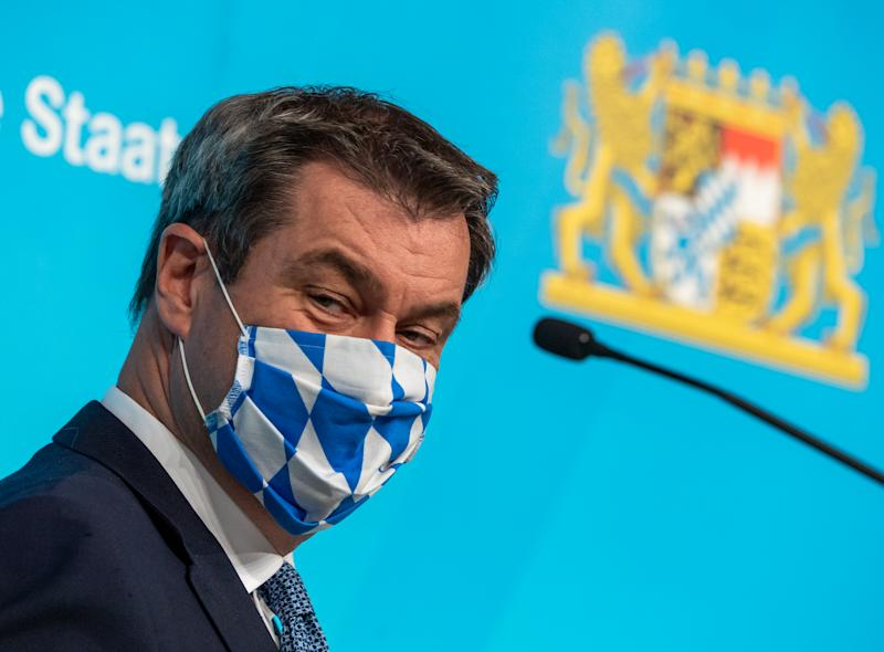 16 June 2020, Bavaria, Munich: Markus Söder (CSU), Prime Minister of Bavaria, puts on his mouth and nose protection mask in a white-blue diamond design after a press conference that took place after the Bavarian cabinet meeting. Photo: Peter Kneffel/dpa (Photo by Peter Kneffel/picture alliance via Getty Images)