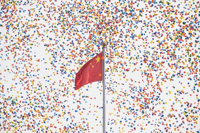 Balloons fly past a national flag at the end of the military parade in Tiananmen Square (AFP Photo/GREG BAKER)