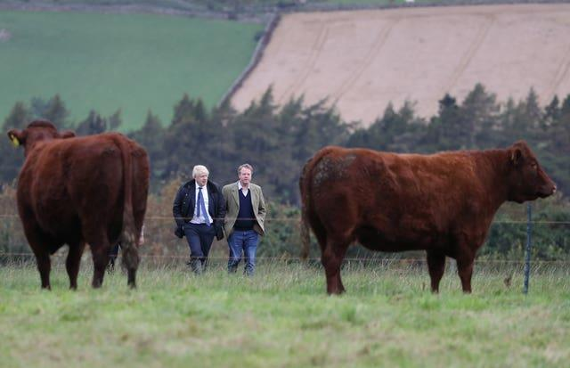 Prime Minister Boris Johnson (left) during a visit to Darnford Farm in Banchory near Aberdeen (Andrew Milligan/PA)