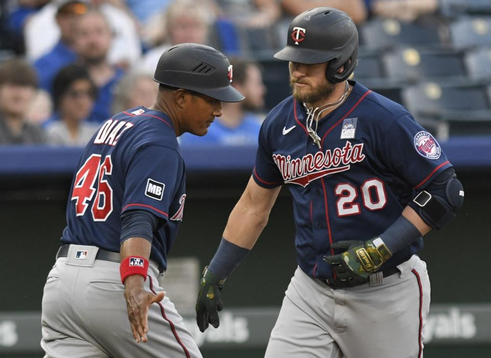 Minnesota Twins' Josh Donaldson (20) is congratulated by third base coach Tony Diaz (46) after hitting a home run against the Kansas City Royals during the first inning of a baseball game Thursday, June 3, 2021, in Kansas City, Mo. (AP Photo/Reed Hoffmann)