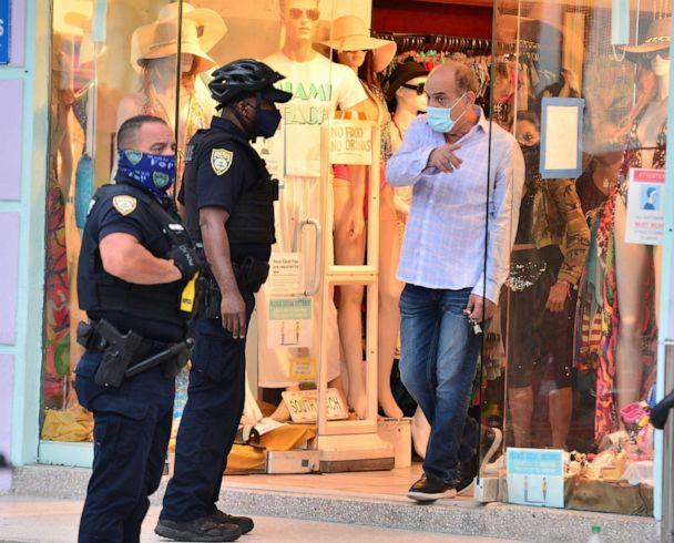 PHOTO: Miami Beach Police officer talks to a shop owner during patrol on Ocean Drive on in Miami Beach, Fla., July 15, 2020. (Johnny Louis/Getty Images)