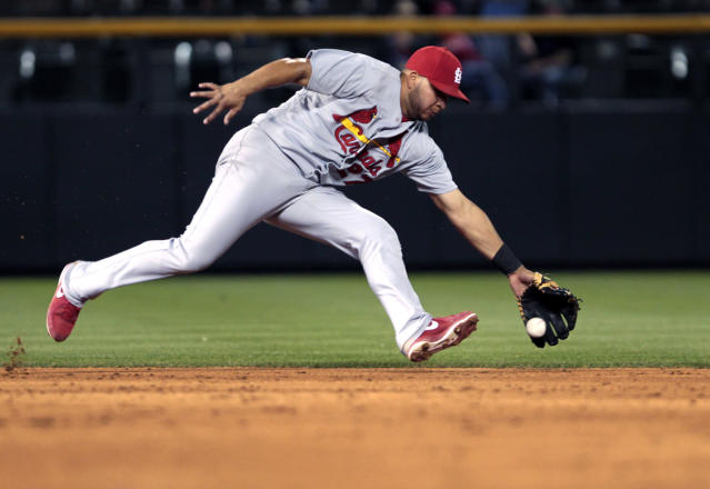 St. Louis Cardinals shortstop Jhonny Peralta fields a ground ball hit by Colorado Rockies' Brandon Barnes before throwing out Barnes at first base to end the sixth inning of a baseball game in Denver on Tuesday, June 24, 2014. (AP Photo/Joe Mahoney)