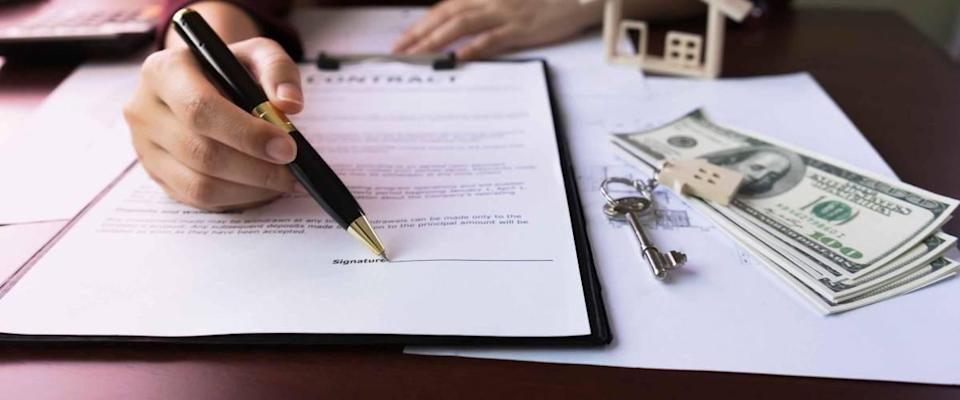 Hand pointing signature of the  real estate agent Client in contract form on table with  money, contract  purchase, house key, house design document.