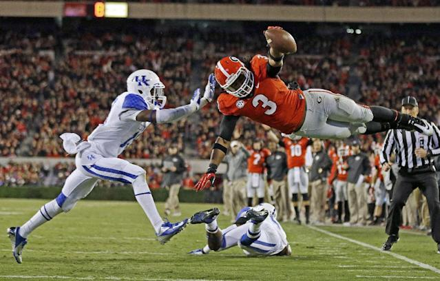 Georgia running back Todd Gurley (3) dives into the end zone for a touchdown as Kentucky cornerback Jaleel Hytchye, left, defends in the first half of an NCAA college football game on Saturday, Nov. 23, 2013, in Athens, Ga. (AP Photo/John Bazemore)