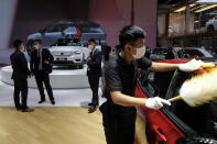 Staff members wearing face masks to help curb the spread of the coronavirus gather near the Volvo car models on display at the Auto China 2020 show in Beijing, Sunday, Sept. 27, 2020. Auto China 2020, postponed from March, is the first major trade show for any industry since the pandemic began as automakers are looking to China, the first major economy to start recovering from the coronavirus pandemic, to drive sales growth and reverse multibillion-dollar losses. (AP Photo/Andy Wong)