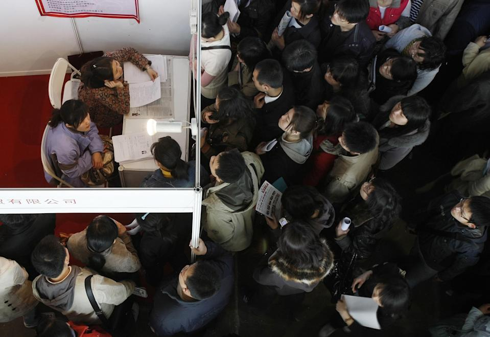 FILE - In this March 25, 2009, file photo, job seekers wait to submit applications at a job fair in Beijing, China. According to a three-month AP investigation released in January 2013, five years after the start of the Great Recession, millions of middle-class jobs have disappeared from the global economy and aren't just being lost to China and other developing countries, but increasingly, jobs are being replaced by technology. (AP Photo/Greg Baker, File)