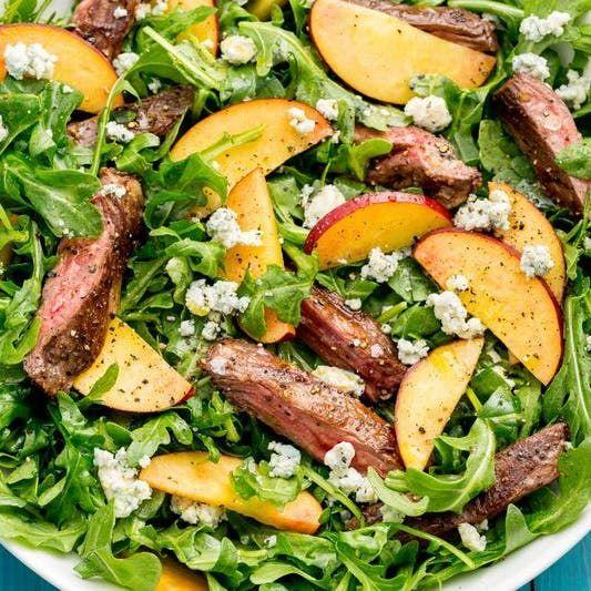"""<p>Peppery rocket is the perfect vessel for this savoury-sweet combo.</p><p>Get the <a href=""""https://www.delish.com/uk/cooking/recipes/a32998377/balsamic-grilled-steak-salad-with-peaches-recipe/"""" rel=""""nofollow noopener"""" target=""""_blank"""" data-ylk=""""slk:Balsamic Grilled Steak Salad with Peaches"""" class=""""link rapid-noclick-resp"""">Balsamic Grilled Steak Salad with Peaches</a> recipe.</p>"""