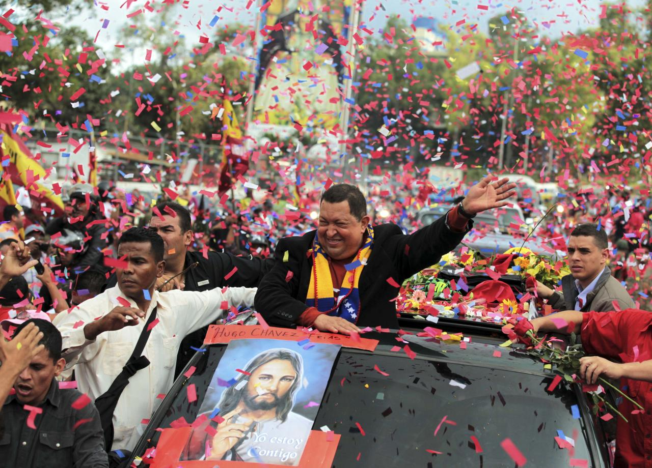 Venezuela's President Hugo Chavez, center, greets supporters during a caravan from Miraflores government palace to Simon Bolivar airport in Caracas, Venezuela, Friday, Feb. 24, 2012. Venezuelan President Hugo Chavez is on his way to Cuba to have a tumor removed from the same region of the pelvis where he had cancer surgery last year. (AP Photo/Fernando Llano)