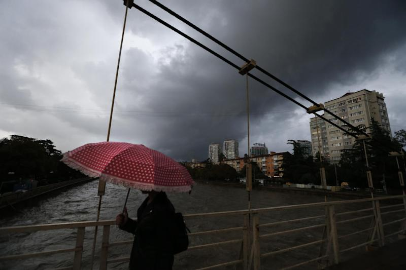 A woman walks across a bridge over Sochi river, where unusually heavy rainfall has caused localized flooding in Sochi, Russia, Tuesday, Sept. 24, 2013. Many critics still complain about underdeveloped infrastructure in Sochi, where the Olympics will be held in February 2014. (AP Photo/Sergei Grits)