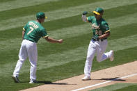 Oakland Athletics' Matt Olson, right, is congratulated by third base coach Mark Kotsay (7) after hitting a home run against the Kansas City Royals during the third inning of a baseball game in Oakland, Calif., Sunday, June 13, 2021. (AP Photo/Jeff Chiu)